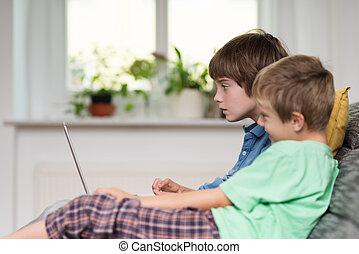 niños jóvenes, sentado, en, un, sofá, juego, en, un, computador portatil