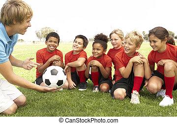 niños jóvenes, y, niñas, en, equipo fútbol, con, entrenador