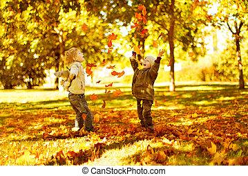 niños jugar, con, otoño, hojas caídas, en el estacionamiento