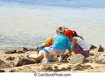 niños jugar, en la playa
