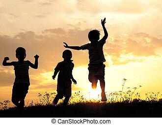 niños que corren, en, pradera, en, ocaso