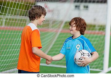 niños, sacudarir las manos, contra, red, en, campo del fútbol