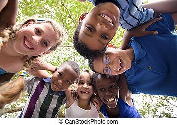 niños, se abrazar, en, círculo, alrededor, el, cámara, y, sonriente