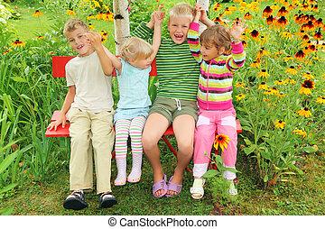 niños, sentar banco, en, jardín, teniendo, manos unidas