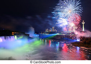 Niagara Falls and fireworks - Niagara Falls lit at night by...