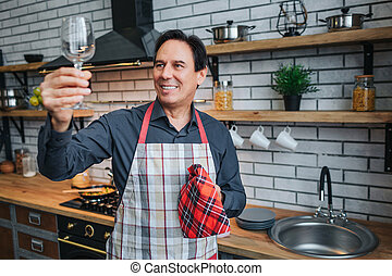 Nice adult man in apron stand alone and look at glass in kitchen. It shine with cleaness. Guy hold kitchen towel and smile