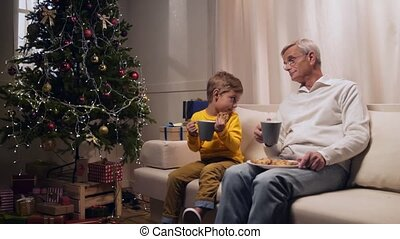 Nice aged man drinking tea with his grandson