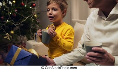 Nice aged man sitting on the sofa with his cute grandson