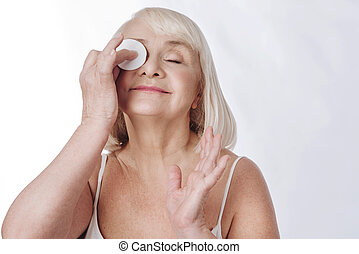 Nice aged woman cleaning her face