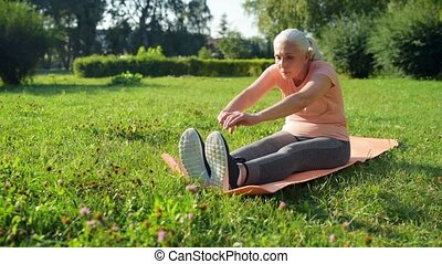Nice aged woman doing sport exercises in the park - Sporty...