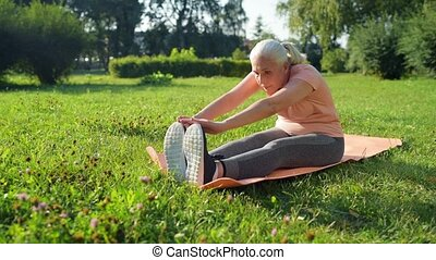 Nice aged woman doing stretching warm up on the exercise mat...