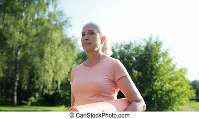 Nice aged woman holding an exercise mat in her hands
