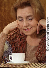nice aged woman sitting on a sofa