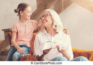 Nice aged woman smiling to her granddaughter