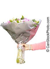 Delicate female hand holding a bouquet of flowers