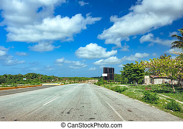 Nice asfalt road with palm trees against the blue sky and cloud. Highway on tropical island. Coastal road in the afternoon. Empty road by the seaside. Green hill, beach, coco palm tree on the roadside. Forest and sea landscape. Summer holiday travel image or banner.