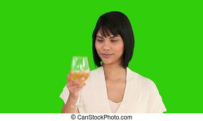 Nice asian woman is enjoying a glass of white wine