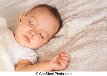 nice newborn sleeps on a white bed