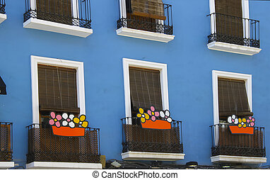 nice balconies with colorful flowers in a blue and white house