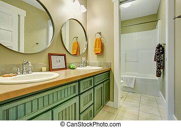Nice bathroom with green cabinets.