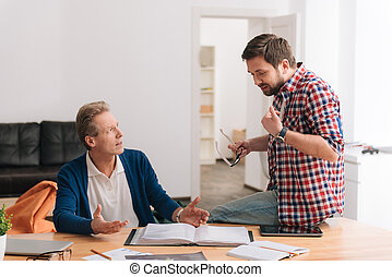 Nice bearded man explaining something to his colleague