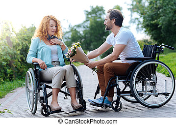 Nice beautiful wheelchaired woman getting a bunch of flowers