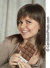 Nice beautiful woman holding a chocolate bar