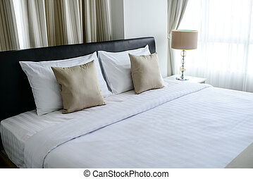 Nice Bed in typical contemporary setting, selective focus.