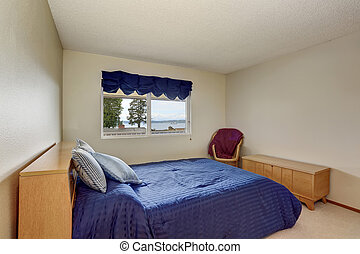 Nice bedroom in creamy tones with small blue bed, wicker chair