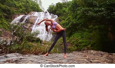 Nice Blond Girl Bends Body in Yoga Pose by Waterfall