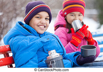 nice boy and girl sitting in park. two persons drinking hot tea outside