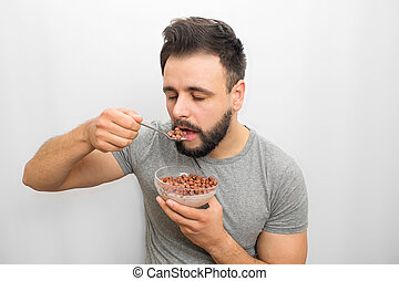 Nice brunette stands and eats chocolate round chips with milk. He is going to put spoon with it in mouth. Guy is sleepy. He looks down. Isolated on white background.