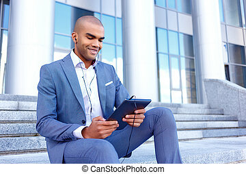 Nice businessman sitting on the stairs