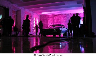 Nice car stand in room while some people walk around