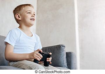 Nice charming boy focused on the game