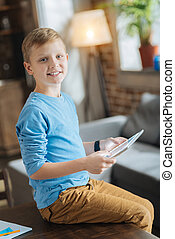 Nice cheerful boy using modern technology