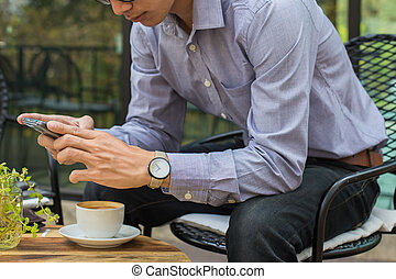 Nice cheerful handsome guy sitting at the table and reads a message on his phone. Business freelance man sitting at table with a laptop in cafe.