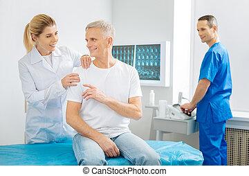 Nice cheerful man speaking to his therapist
