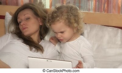 nice child girl looking at tablet computer while mother sleeping in bed