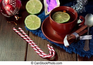 Nice christmas tea on wooden table with lime.