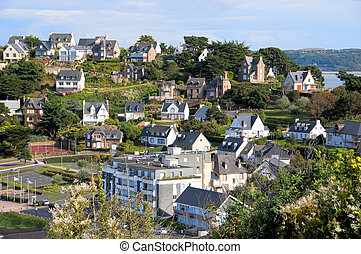 Nice coastal village in sunshine - colored houses on a hill
