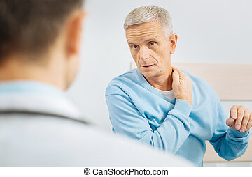 Nice concerned man touching his neck