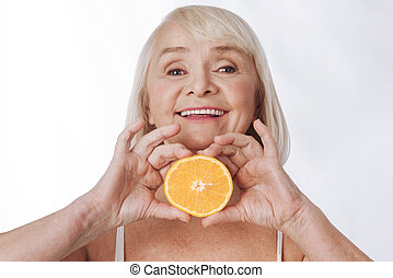 Nice content woman holding an orange