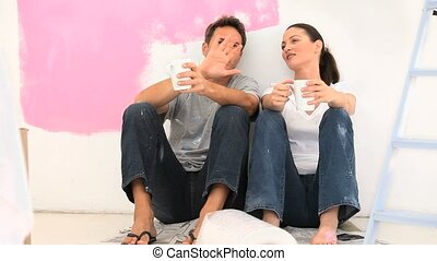 Nice couple drinking after painting their appartment