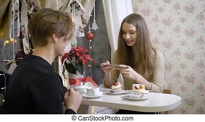 Nice couple of young people in the cafe talk. Girl smiling at her boyfriend, she drinks coffee, warm hands. Beautiful brunette little bit confused and in love.