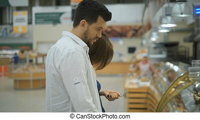 Nice couple of young people, man and woman in the supermarket choosing confectionery.