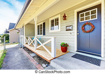 Nice covered porch with blue entrance door