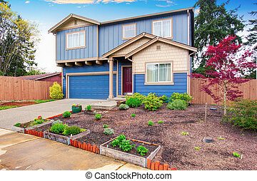 Nice curb appeal of blue house with front garden.