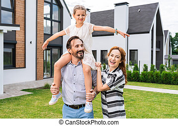 Nice cute girl sitting on her fathers shoulders