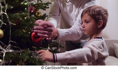 Nice cute little boy decorating Christmas tree